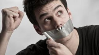Man with tape over his mouth (stock picture)