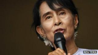 Aung San Suu Kyi addresses supporters and reporters from behind the gates of the National League for Democracy (NLD) office in Yangon 2 April, 2012