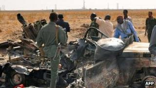 Sudanese troops and onlookers stand next to a burnt out military vehicle in Sudan's southern oil centre of Heglig after South Sudanese troops and government forces clashed along the border (28 March 2012)