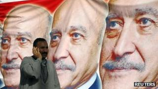 A man stands in front of images of Gen Suleiman at a campaign gathering, 6 April 2012