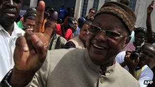 Carlos Gomes Junior flashes the victory sign after casting his vote at a polling station in Bissau on 18 March