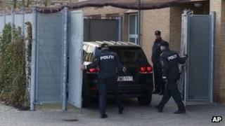 Danish police meet a car carrying one of the defendants to court in Glostrup, Copenhagen, 13 April