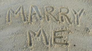 Marry Me written in sand