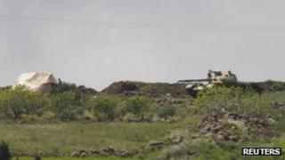 A Syrian tank takes position as seen from the Wadi Khalid area near the Syrian border, in northern Lebanon April 12, 2012