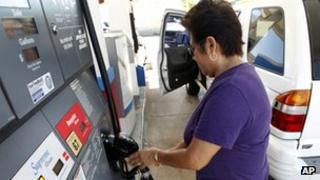 A lady filling her car with gasoline