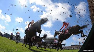 Riders race each other during the Grand National