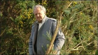 Dafydd Wyn Wiliam yn torri eithin ger cofgolofn y Morrisiaid ym Mhentre-eiriannell, Ynys Môn. Llun trwy garedigrwydd JR Williams ar ran Cymdeithas Morrisiaid Môn