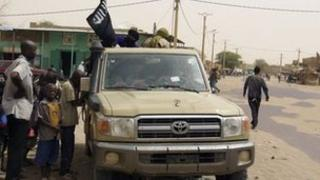 In this Saturday, 14 April, 2012 photo, fighters from the Ansar Dine group, flying the group's black flag, instruct local residents in how to follow Sharia law, as they stop in a market area of Timbuktu, Mali.