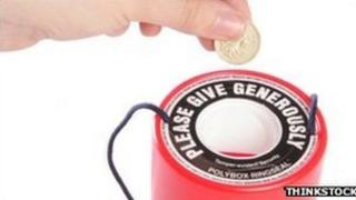 Person placing money in charity collection tin (generic)