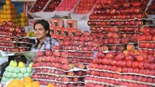 An Indian fruit vendors waits for customers