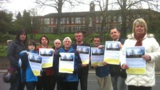 Campaigners stand behind the old entrance of Maltby grammar school which they are hoping to save from demolition