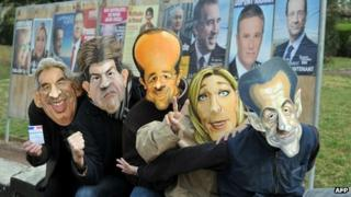 Employees of the Cesar mask-making company pose in front of electoral billboards wearing 2012 French presidential election candidates' masks in Saumur, western France, 18 April