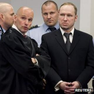 Anders Behring Breivik (R) with his lawyer Geir Lippestad (L) and guards in court (18 April)