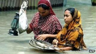 Bangladeshi wade through floodwaters