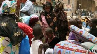 Women and children stand with their baggage as they wait for a place on a vehicle to flee Timbuktu, Mali - 11 April 2012