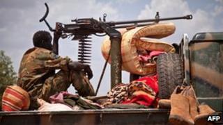 South Sudanese soldier sitting next to a machine gun
