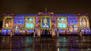 Buckingham Palace projected with images of the Queen and school children's self portraits