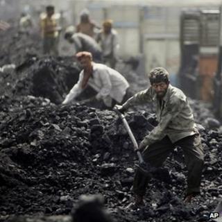 Man shovelling coal at a depot in Jammu, India