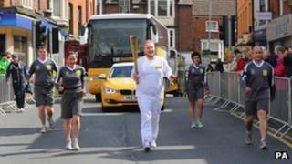 Torchbearer James Mott carries the torch during a dress rehearsal for the Torch Relay