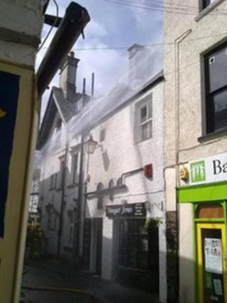 The fire in the roof being put out. Photo by Louise McMahon from Love the Lakes