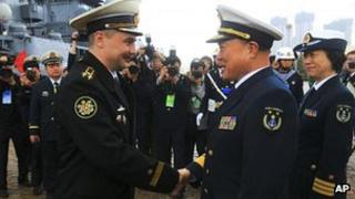 Rear Adm. Du Xiping, front right, deputy commander of China's Beihai Fleet, shakes hands with Captain First Rank Sergei Yuriyevich Zhuga of Russia's Pacific Fleet during a welcome ceremony at a naval base in Qingdao, China, 21 April 2012