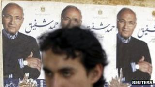 A man walks past posters for Ahmed Shafiq (5 April 2012)