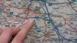 Finger pointing at a map