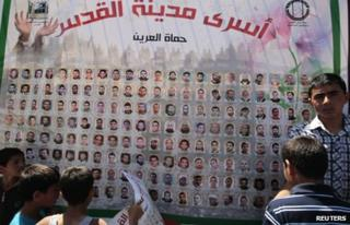 Palestinian boys look at a poster showing inmates on hunger strike (20 April 2012)