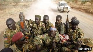 South Sudan's army, or the SPLA, soldiers drive in a truck on the front line in Panakuach, Unity state