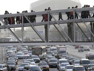 Pedestrians walk on a sky bridge in downtown Beijing (file photo)