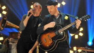 Chris Martin and Jonny Buckland on stage