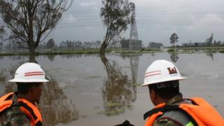 Engineers travelling through flooded areas by dinghy
