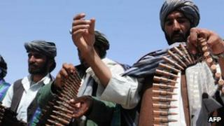Former Taliban fighters display their weapons as they join Afghan government forces during a ceremony in Herat province on April 26, 2012.