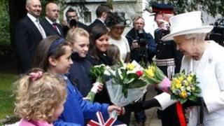 The Queen receives flowers from Georgie Seager, nine, as she leaves Llandaff Cathedral