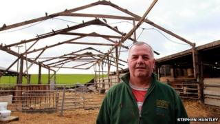 Farmer Alan Barrow stood beside a barn that blew over in high winds