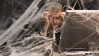 Man at desk covered in cobwebs