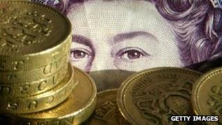 Pound coins in front of £20 note