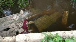 The brick wall of the bridge which fell into the stream in West Stafford