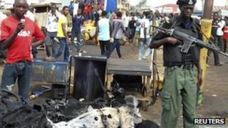 A member of the armed forces stands guard by part of a car used to detonate a bomb is seen at the scene of a blast in Nigeria's northern city of Kaduna on 8 April 2012