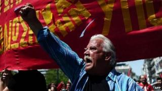 Man holding his fist in the air at a rally in Athens