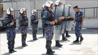 Palestinian women police officers stand behind policemen with riot shields in training