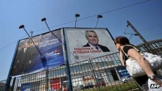 A woman passes billboards in Belgrade advertising Boris Tadic (left) and Tomislav Nikolic, 3 May