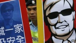 A police officer stands guard in the middle of two images featuring blind Chinese activist Chen Guangcheng during a protest in front of the Chinese central government's liaison office in Hong Kong on 4 May 2012