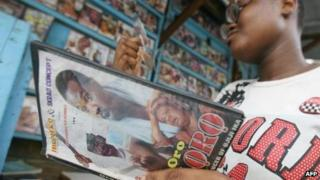 A young Ivorian looks the DVD of a Nollywood (combination of Nigeria and Hollywood) film in a street store in Abidjan, 16 June 2007.