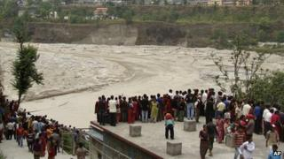 People in Nepal's Kaski district watch the flooded Seti River (5 May)