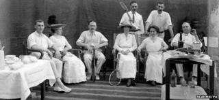 Undated photo of a group of people posing for a photograph during a tennis party at least 100 years ago