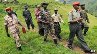 Rebel General Ntaganda Bosco (2ndR), self declared leader of the National Committee for the Defence of the People (CNDP) walks escorted by comrades on January 11, 2009 at his mountain base in Kabati, 40km north west of the provincial capital Goma