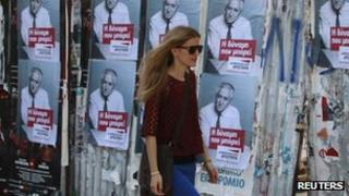 Woman walks past Greek election posters