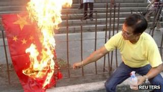 An activist burns a flag of China during a rally in front of the Chinese consular office in Makati's financial district of Manila on 8 May, 2012