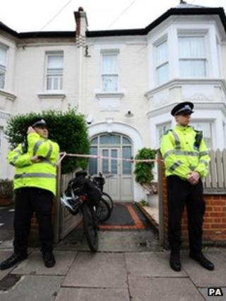 Police officers stand outside the home in Wandsworth